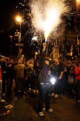 A man sets off fireworks in the middle of the crowd celebrating President-elect Barack Obama's election night victory